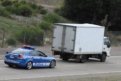追逐警察卡车的汽车 免版税库存照片