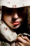 注视隐藏神奇被修饰的披肩的女孩 免版税库存照片