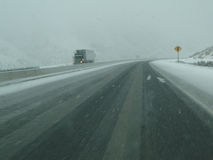 牵引车拖车在冰冷的路慎重地驱动  免版税库存照片
