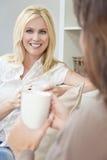 Δύο φίλοι γυναικών που πίνουν το τσάι ή τον καφέ στο σπίτι Στοκ φωτογραφία με δικαίωμα ελεύθερης χρήσης