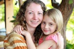 拥抱母亲的女儿 免版税库存图片
