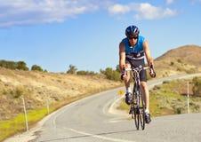 路的男性骑自行车者 库存照片