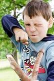 淘气恼怒的男孩森林的枪 免版税库存图片