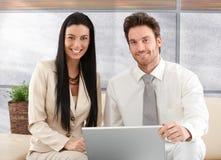 微笑典雅的夫妇浏览的互联网在家 免版税库存图片