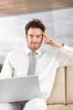 与膝上型计算机微笑的英俊的生意人 免版税库存照片