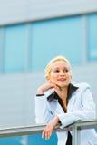 倾斜在用栏杆围的女商人在办公室 免版税图库摄影