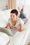 使用膝上型计算机的一名深色头发的妇女的纵向 免版税库存照片