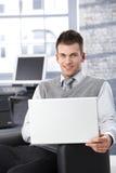研究膝上型计算机的微笑的人 免版税库存照片