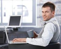 偶然生意人用茶和膝上型计算机 免版税图库摄影