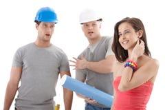 凝视俏丽的女孩的承包商工作者 免版税库存照片