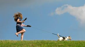 儿童狗走的年轻人 免版税库存照片