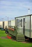 在绿草的有蓬卡车阵营在云彩之下 免版税库存照片