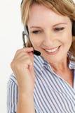 使用耳机的中间年龄女商人 免版税图库摄影