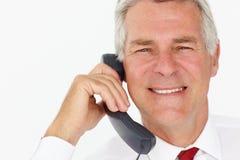 在电话的高级生意人 库存图片