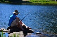 男孩少年捕鱼的湖 库存照片