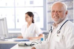 坐在服务台微笑的高级医生 免版税库存照片