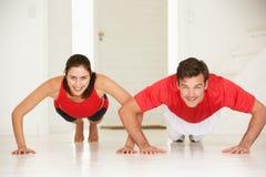 耦合执行俯卧撑在家庭体操方面 免版税库存照片