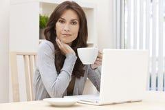 用膝上型计算机饮用的茶或咖啡的妇女 免版税库存图片