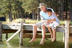 老人和孙子捕鱼 库存图片