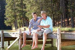 有父亲和成人的儿子乐趣捕鱼 免版税库存照片