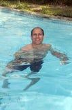 年龄英俊的人中间池微笑的游泳 免版税库存照片