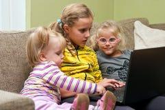 女孩膝上型计算机沙发 免版税库存照片
