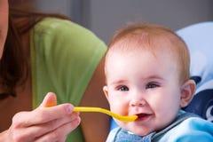 喂养饥饿的母亲的婴孩 库存图片