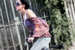 骑自行车的女孩年轻人 免版税库存图片