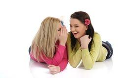 说闲话的女孩相当二个年轻人 免版税库存照片