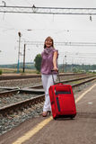 带着一个红色手提箱的少妇 免版税库存照片
