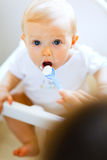 婴孩椅子吃提供的母亲被抹上 库存照片