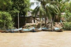 沿钓鱼小屋湄公河的小船 免版税库存照片