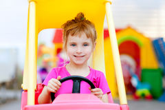 驾驶女孩玩具的白肤金发的汽车子项 免版税库存图片
