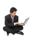 Το νέο επιχειρησιακό άτομο κάθεται χρησιμοποιώντας το σημειωματάριο Στοκ φωτογραφίες με δικαίωμα ελεύθερης χρήσης