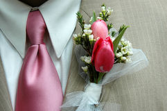 钮扣眼上插的花粉红色关系 库存图片