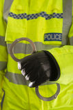 拿着官员警察的手铐 免版税库存照片
