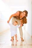 走的婴孩愉快的帮助的妈妈 库存照片