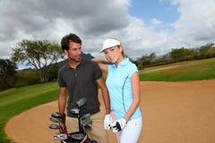 打高尔夫球的夫妇 库存照片