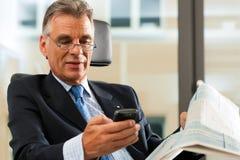 检查电子邮件的上司他的办公室 免版税库存图片