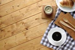 咖啡新月形面包木杯子的表 免版税库存照片