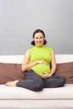 家庭怀孕的坐的沙发妇女 库存照片
