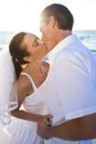 新娘&新郎夫妇亲吻的日落海滩婚礼 免版税库存照片