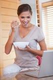 吃谷物的妇女在她的膝上型计算机旁边 库存照片