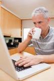使用膝上型计算机的一个人的纵向,当喝咖啡时 图库摄影