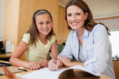 做家庭作业的母亲和女儿 免版税库存图片