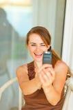 采取照片她自己的微笑的妇女在移动电话 免版税库存照片