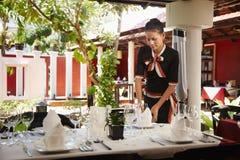 亚洲女服务员设置表在餐馆 免版税库存照片