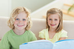 读小册子的兄弟姐妹在沙发 免版税图库摄影