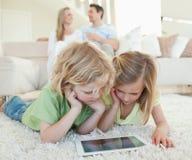 在地板上的孩子与在他们之后的片剂和父母 免版税库存图片
