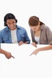 指向下来在死墙上的微笑的夫妇 免版税库存图片